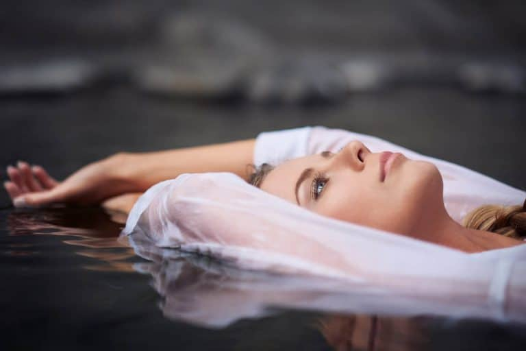 Woman floating in a creek.
