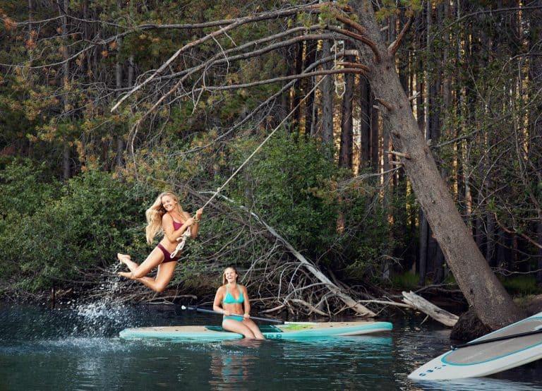 Two young women enjoying a rope swing on a small mountain lake.