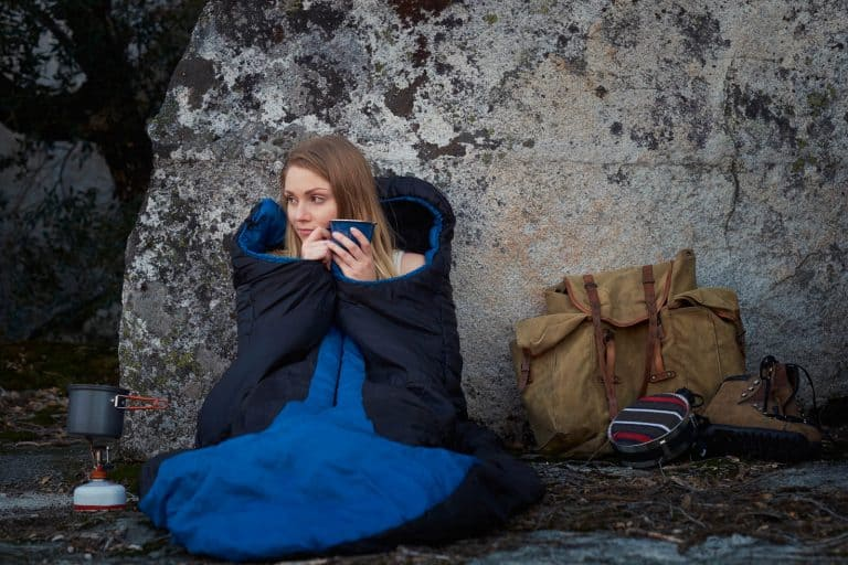 Enjoying coffee outdoors while still in a sleeping bag.