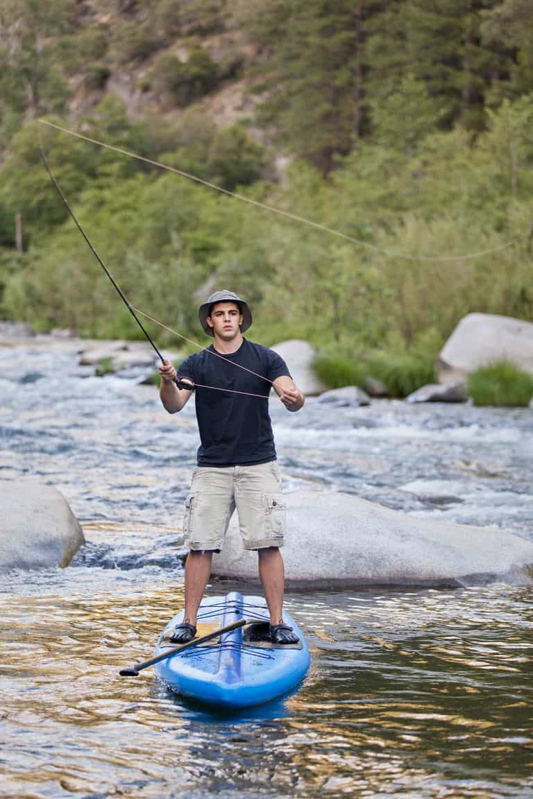 A young man flyfishing from a paddle board in a the rapids of the Feather River in Northern California.