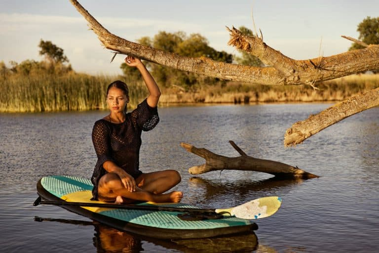 A young, attractive woman relaxing on a paddle board on a small lake in Northern California.