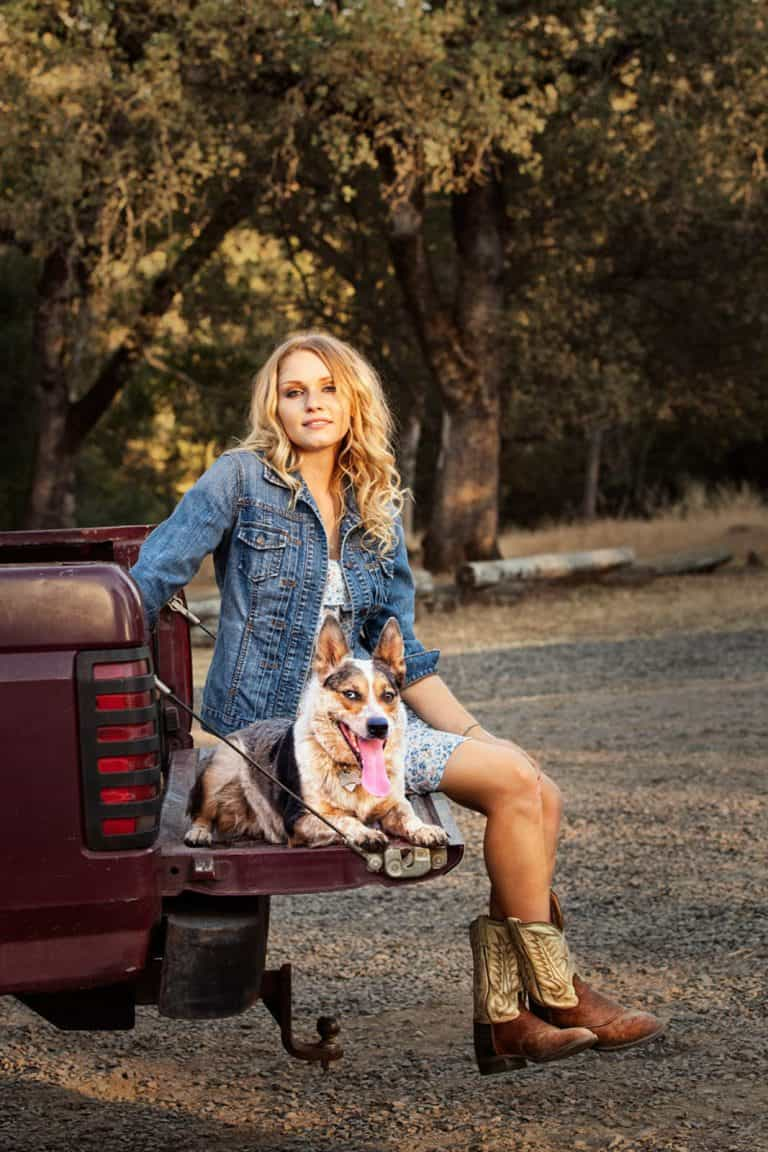 country girl on a truck tail gate with her dog.