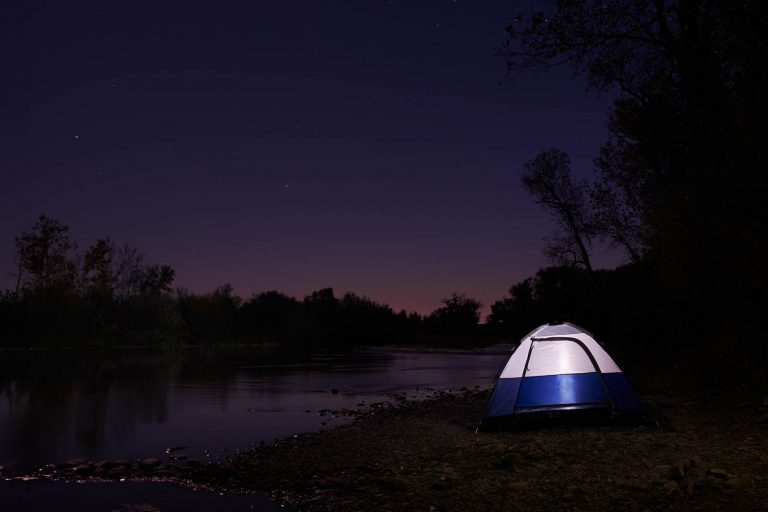 An illuminated tent on the edge of the Feather River in Northern California at night