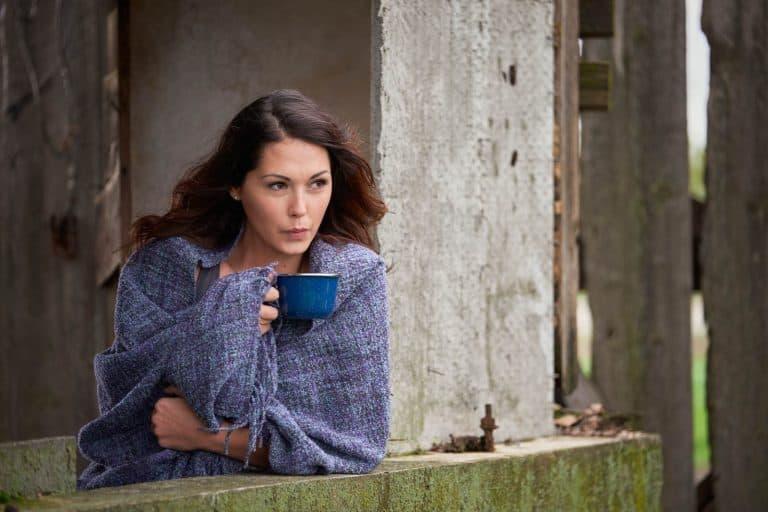 Woman on a farm drinking coffee.
