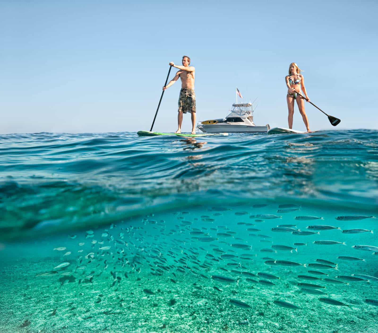 A young couple paddle boarding over clear ocean waters full of fish.