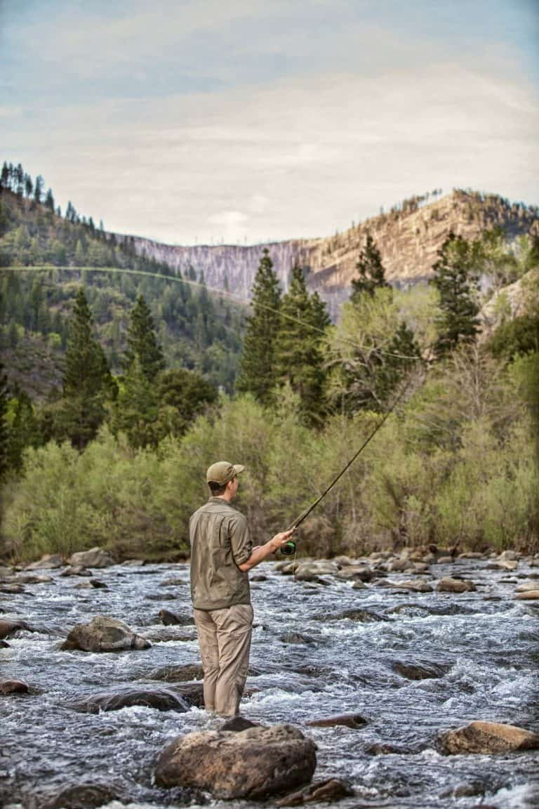 Fly fisherman in a small mountain river.
