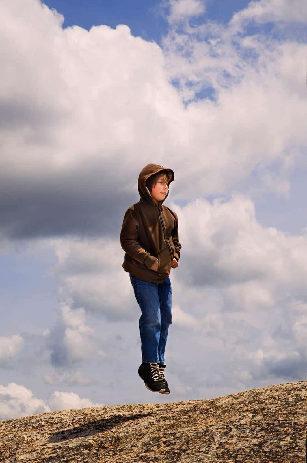 A young boy jumping on a granite boulder while enjoying a sunny spring day in Northern California.