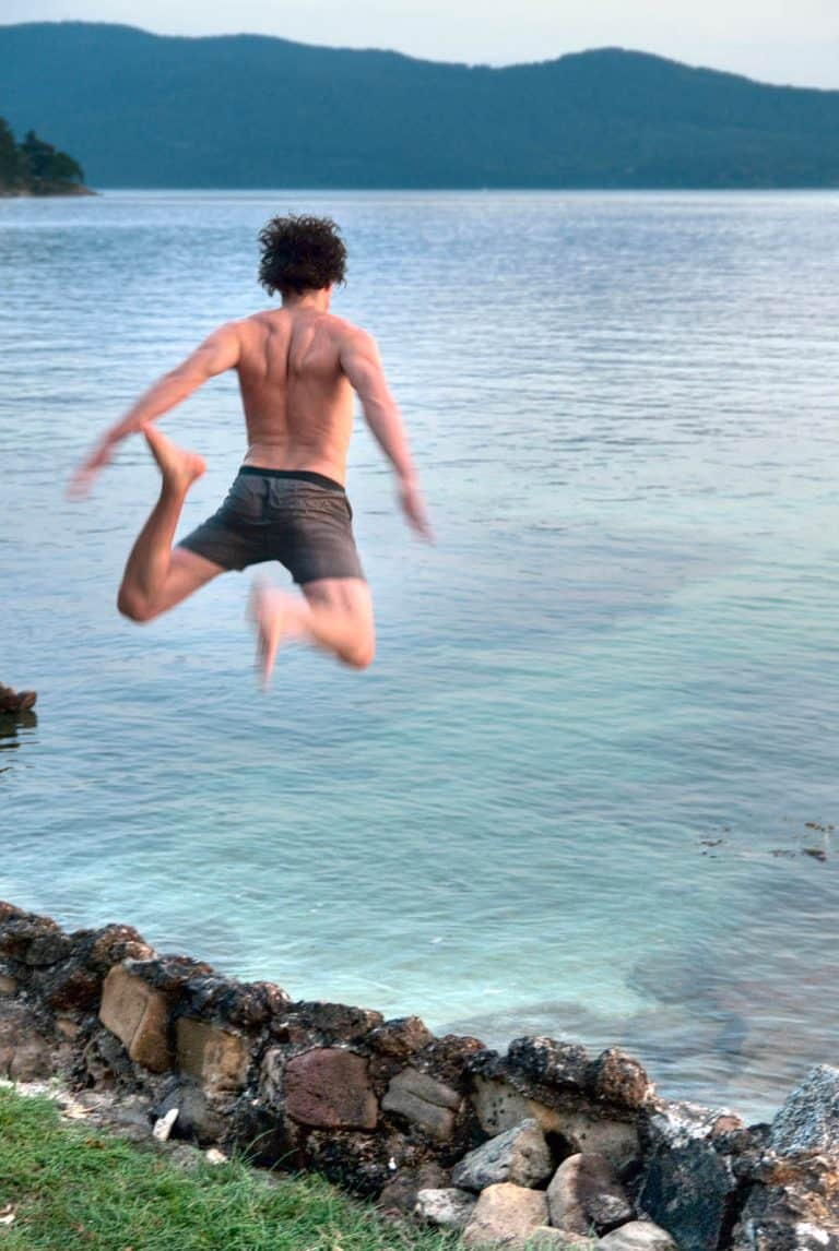 Jumping over a rock wall into the ocean.