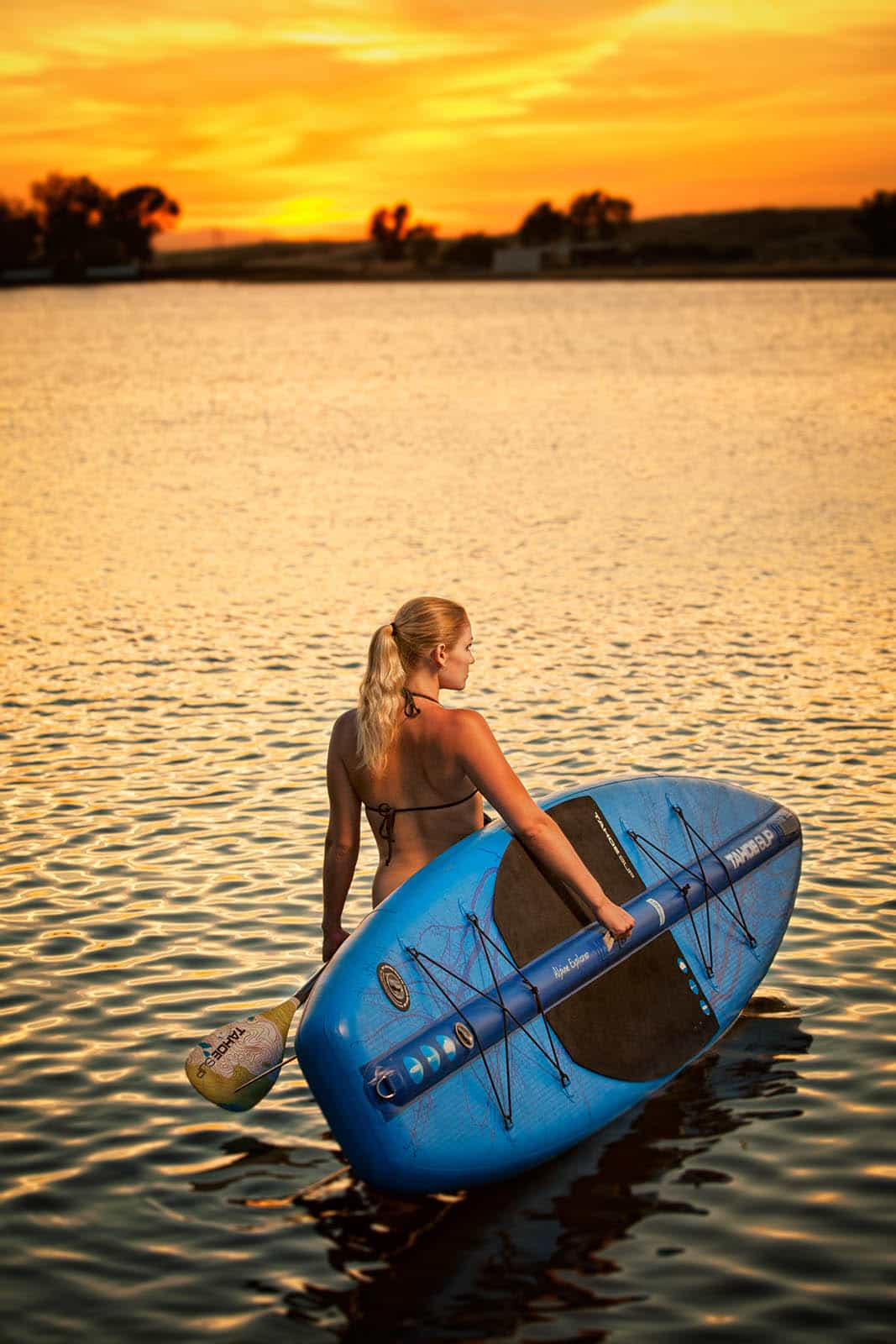 A young woman wading into a small lake with a paddle board at sunset.