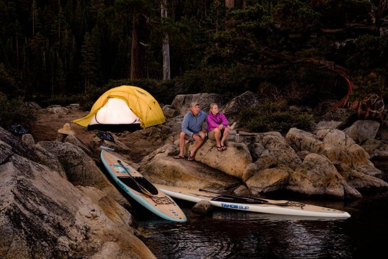 A couple relaxing at their campsite after paddle boarding