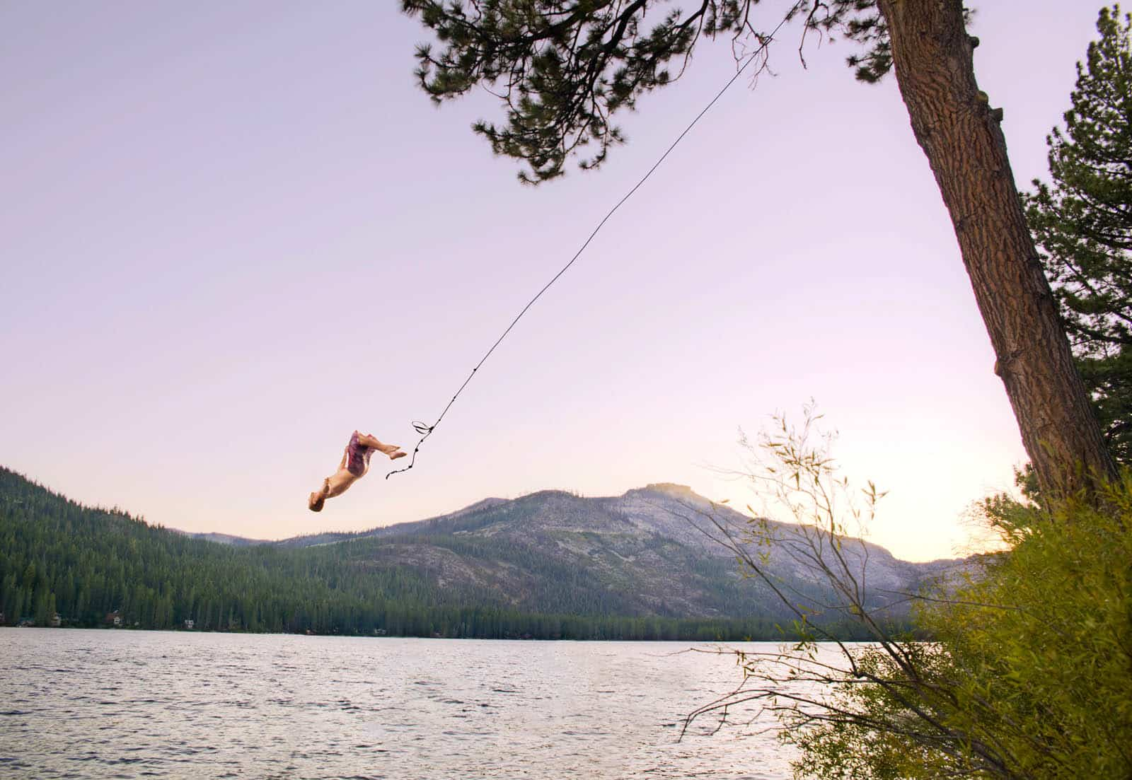 A you man doing a backflip off a rope swing.