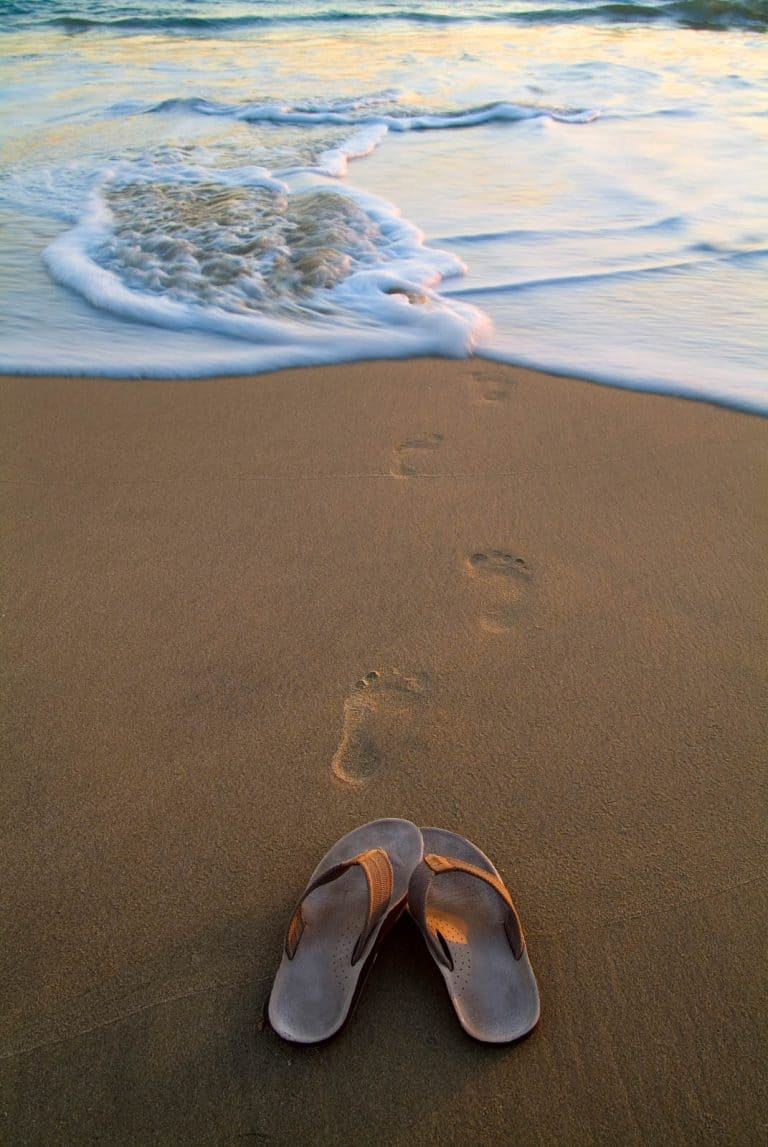 Sandals on a beach in Southern California with footprints in the sand leading towards the water.